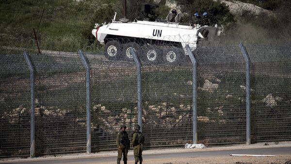 Israeli soldiers (front) stand near the frontier with Syria as members of United Nations peacekeeping force head to retrieve bodies of four killed by an Israeli air strike, in the Golan Heights April 27, 2015. - Sputnik 日本