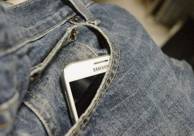 Телефон марки Samsung в кармане джинсов