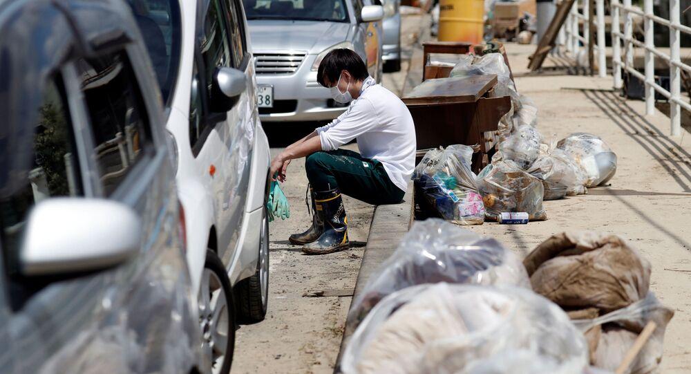 清掃作業の手を休めて一息つく住民。岡山県真備町
