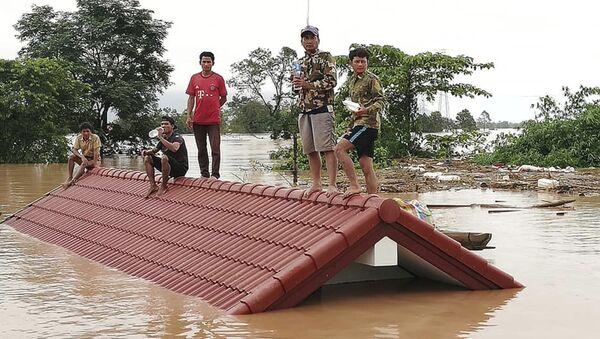 Селяне спасаются от наводнения, вызванного прорывом дамбы, на крыше дома в юго-восточной лаосской провинции Аттапы - Sputnik 日本