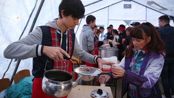 Волонтер разливает горячий чай для пассажиров поезда, задержанных в Краснодарском крае из-за наводнения - Sputnik 日本