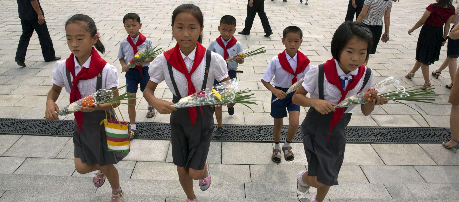 Школьники несут цветы к памятникам северокорейским лидерам Ким Ир Сена и Ким Чен Ира в Пхеньяне в годовщину окончания Второй мировой войны и освобождения от японского колониального правления  - Sputnik 日本, 1920, 21.01.2021