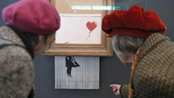 Посетители смотрят на самоуничтожившуюся после продажи на аукционе картину художника Бэнкси Девочка с воздушным шаром, которая теперь называется Любовь в мусорном баке, в Музее современного искусства в Баден-Бадене, Германия - Sputnik 日本