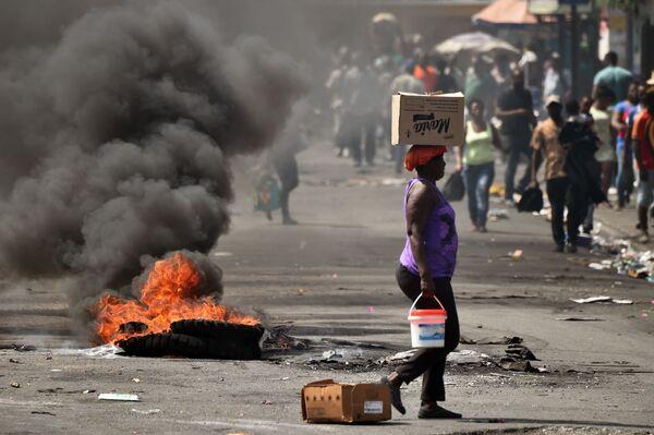 ハイチの首都ポルトープランスで、路上で燃えるタイヤのそばを通り過ぎる女性 - Sputnik 日本