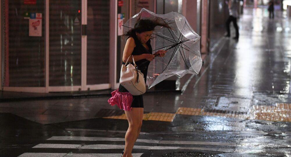 強風の中で傘を握り締める女性 東京