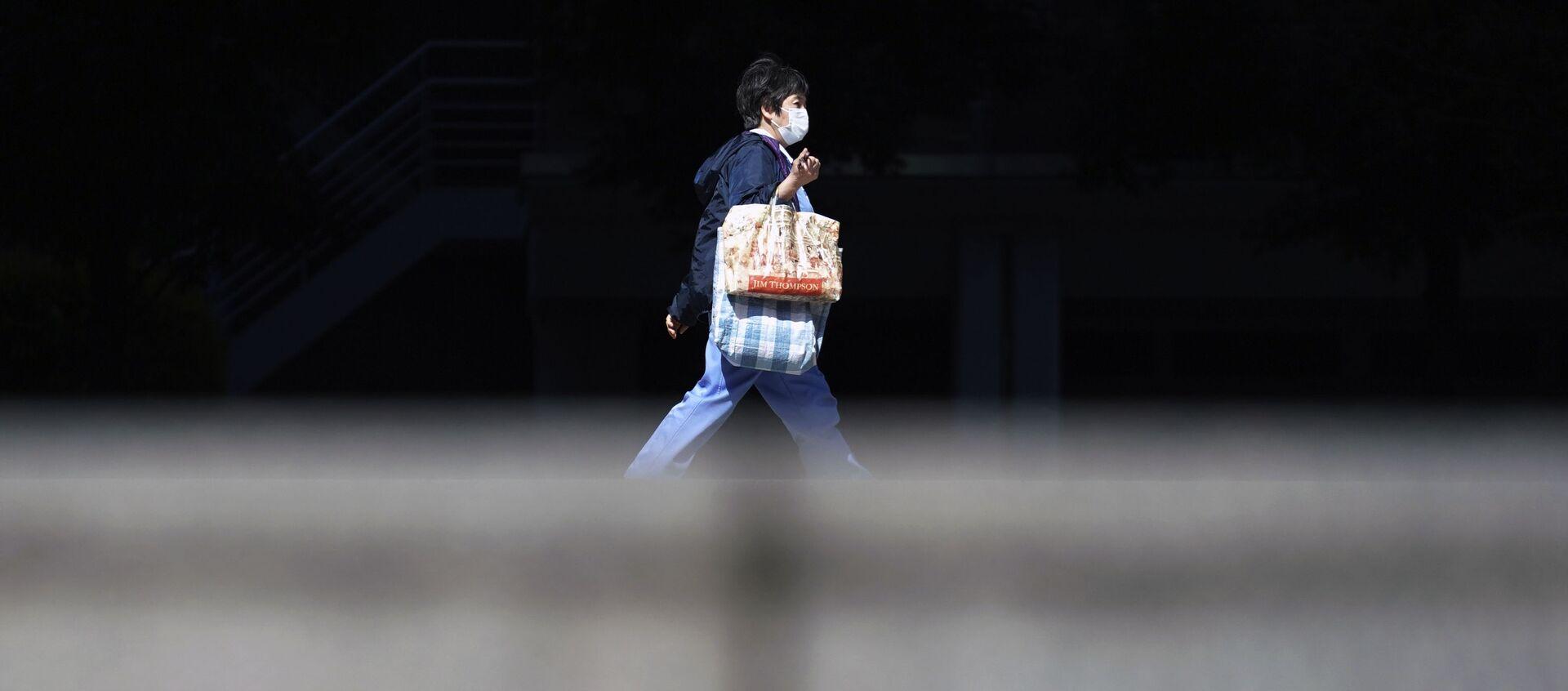 Женщина в защитной маске идет по улице в Токио, Япония - Sputnik 日本, 1920, 01.01.2021